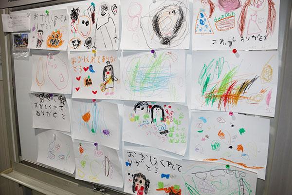 会社の壁に飾られている、絵や文字で描かれた子どもたちの収穫体験の感想。